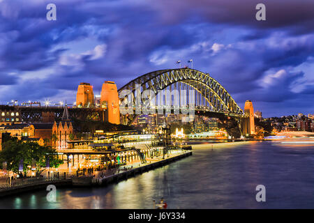 Huge illuminated arch of Sydney Harbour bridge connecting city CBD from the Rocks to North Sydney. Bright lights - Stock Photo