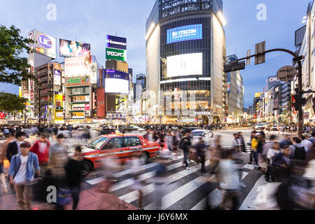 TOKYO - MAY 3, 2017: A taxi is stuck among the crowd crossing the famous Shibuya crossing at night in Tokyo, Japan - Stock Photo