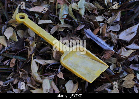 An abandoned and faded yellow child's toy spade - Stock Photo
