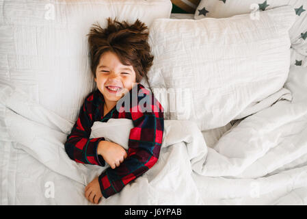Portrait of a boy lying in bed laughing - Stock Photo