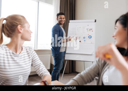 Positive delighted man looking at his colleagues - Stock Photo