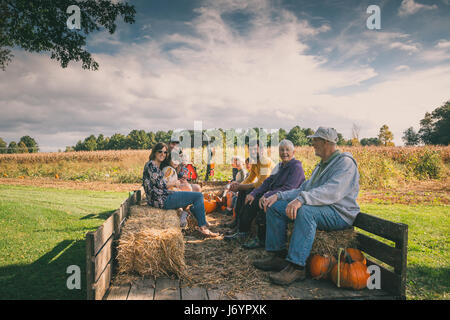 Multi-generation family sitting in a wagon at a pumpkin patch - Stock Photo