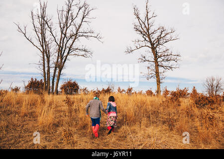 Boy and girl holding hands running in rural landscape - Stock Photo