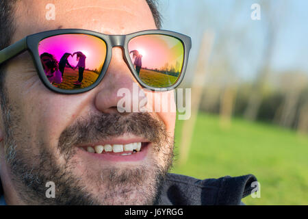 Two children making heart shape with their hands reflected in man's sunglasses - Stock Photo