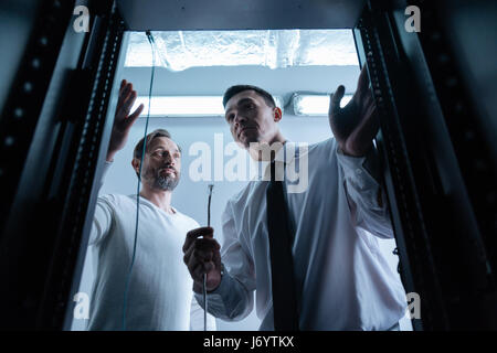 Serious professional technician holding Ethernet cable - Stock Photo
