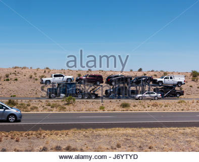 Semi tractor trailer hauling cars on I-10 in southeastern Arizona , driver visible in car - Stock Photo
