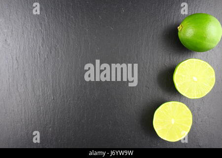 fresh lime fruit on a slate plate as a food background texture - Stock Photo