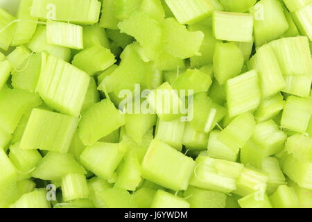 fresh peeled and cutted rhubarb leaf stalks as a food background texture - Stock Photo