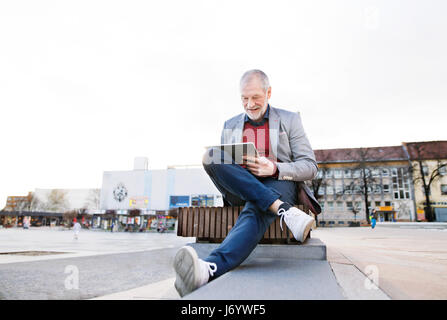 Senior man in town sitting on bench, working on tablet - Stock Photo