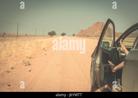 Woman's legs leaning out from car standing on gravel road in the Namib desert, Namib Naukluft National Park, main - Stock Photo