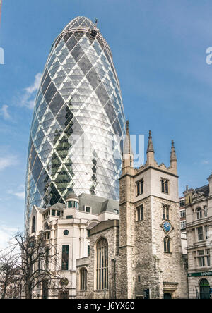 The historic St. Andrew Undershaft Church with 30 St. Mary Axe towering above it in the City of London - Stock Photo