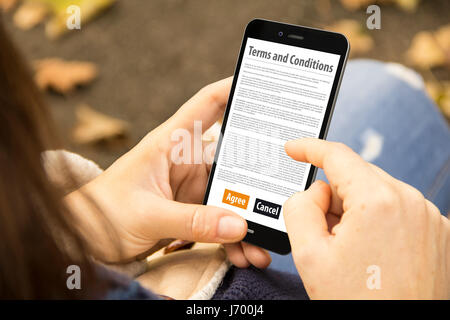 mobile concept: woman holding a 3d generated smartphone with terms and conditions on the screen. Graphics on screen - Stock Photo