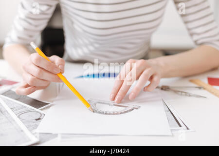 Skillful female engineer using a protractor - Stock Photo
