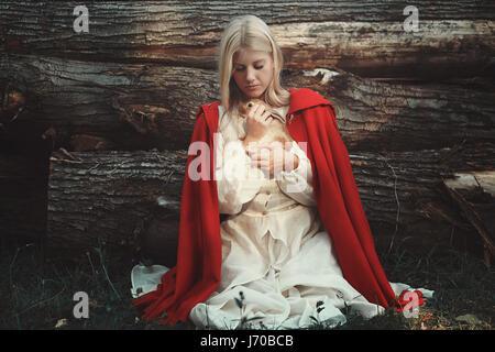 Blond woman hugging little sweet rabbit. Animal protection