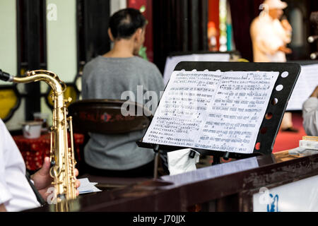 April 2017 - Guangzhou, China. Chinese Opera musician playing a tenor saxophone while reading Chinese music sheet. - Stock Photo