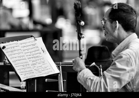 April 2017 - Guangzhou, China. Chinese Opera musician playing the Erhu while reading Chinese music sheet. - Stock Photo