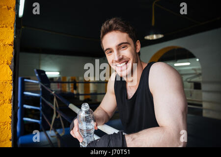Side view of a smiling boxer relaxing in boxing ring in gym, drinking water and looking at the camera - Stock Photo