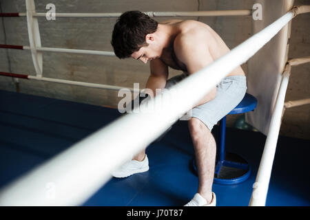 Thoughtful tired sportsman after training sitting in corner of ring and looking down - Stock Photo