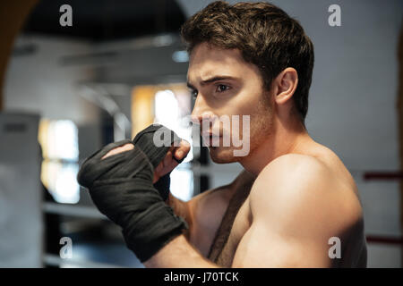 Focused young boxer wearing black gloves training in gym - Stock Photo