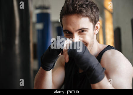 Close up  view of smiling boxer doing exercise in gym and looking at the camera - Stock Photo