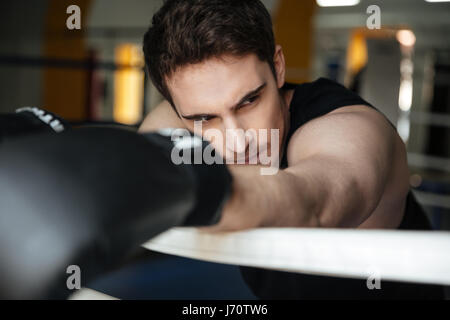 Portrair of tired young sportsman after training leaning on boxing ring in gym - Stock Photo