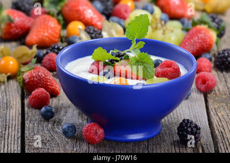 Plain yogurt with mixed fresh fruit in a blue ceramic bowl on a wooden table - Stock Photo