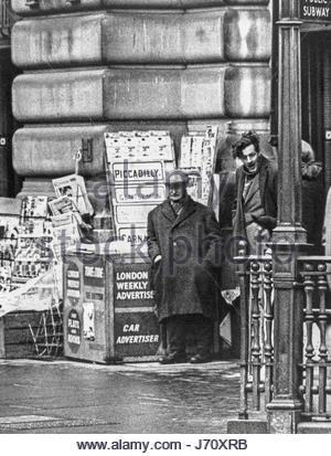 London 1960s; newspaper vendor street trader in the rain at Piccadilly, London, England, UK – 1960s (1967) - Stock Photo