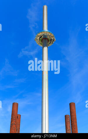 Brighton i360 observation tower on the seafront, with the rusty pier supports of the old West Pier in the foreground. - Stock Photo
