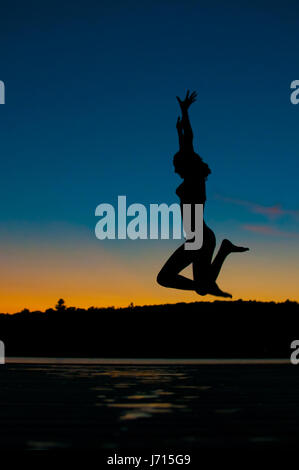 silhouette of a teenage girl jumping off a dock into a lake at sunset - Stock Photo