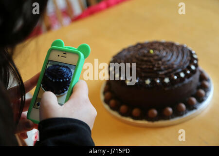 Woman taking photo with mobile phone of Home made Chocolate Cake with maltesers - Stock Photo