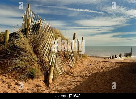 A gap in the fence along sand dunes, overlooking the sea. - Stock Photo