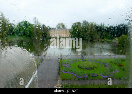 Blurred view looking out across the lake through rain on glass window from inside the Palm House at Kew Gardens - Stock Photo