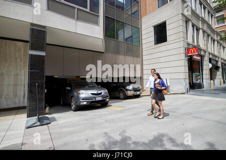couple walking past car coming out of underground and multi storey parkade parking garage downtown Washington DC USA