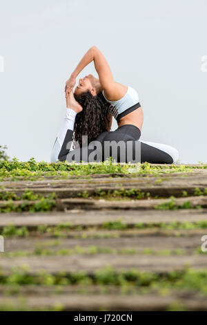 woman practicing yoga outside - Stock Photo