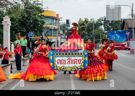 Chiang Mai, Thailand - August 24, 2016: Young girls and boys in festival costumes parade near the Three Kings Monument - Stock Photo