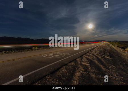Route 66 sign with full moon and streaking train in the California Mojave desert. - Stock Photo