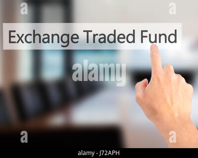 Exchange Traded Fund - Hand pressing a button on blurred background concept . Business, technology, internet concept. - Stock Photo