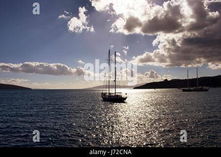 Sun light breaks through clouds in dramatic sky. It shines on sea surface in Bodrum southwestern Turkey. Reverse - Stock Photo