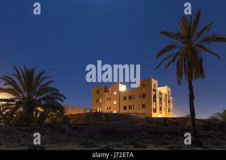 Starry sky, a building and palm trees in Tabounte, Tarmigte, Souss-Massa-Draa, Morocco - Stock Photo