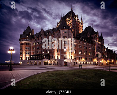 Fairmont Le Château Frontenac with dramatic night sky lit by street lights, grand hotel Chateau Frontenac. Old - Stock Photo