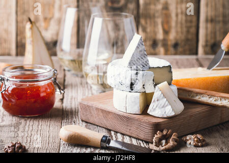 Cheese platter served with white wine, jam and walnuts on wooden board on rustic table - Stock Photo