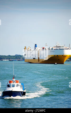 Tug boat and car transporter Grimaldi Lines approaching the port of Southampton in 2017, Southampton Water, UK - Stock Photo