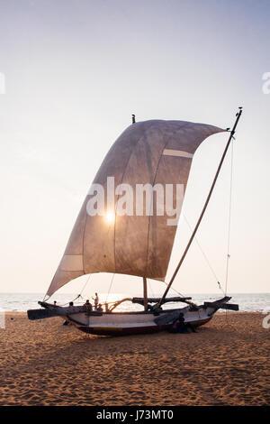 Traditional fishing boat at Negombo beach, Sri Lanka at sunset with the sun shining through the sail. - Stock Photo