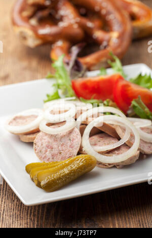 bavarian sausage salad with a pretzel - Stock Photo