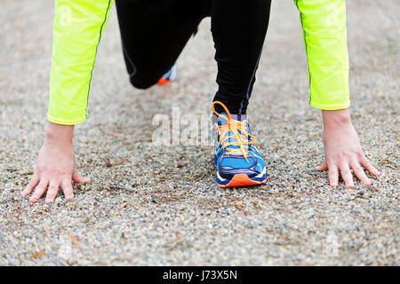 A professional runner preparing for the start on the start line - Stock Photo