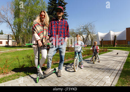 Couple with children on scooters - Stock Photo