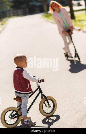 Woman with son on scooters - Stock Photo