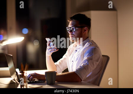 businessman texting on smartphone at night office - Stock Photo
