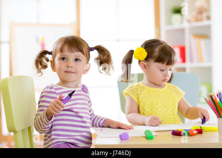 Kids drawing in kindergaten. Children paint in nursery. Preschooler with pen at home. Creative toddler. - Stock Photo