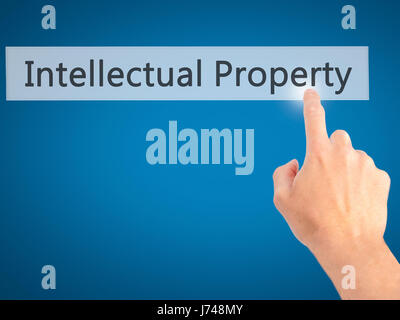 Intellectual Property - Hand pressing a button on blurred background concept . Business, technology, internet concept. Stock Photo